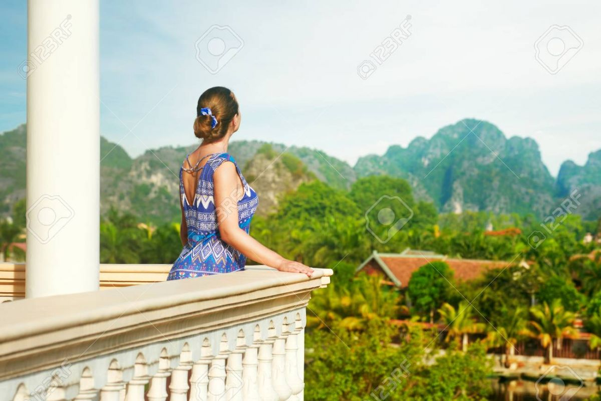 81856447-woman-standing-on-the-balcony-watching-beautiful-mountains-view-travel-and-relaxation-concept-.jpg